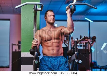 Powerful Athletic Bodybuilder Standing On A Parallel Bars In A Modern Fitness Center Looking Relaxed