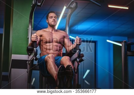 Powerful Athletic Bodybuilder Doing Excersise On A Parallel Bars, Pumping His Abs And Lifting His Le