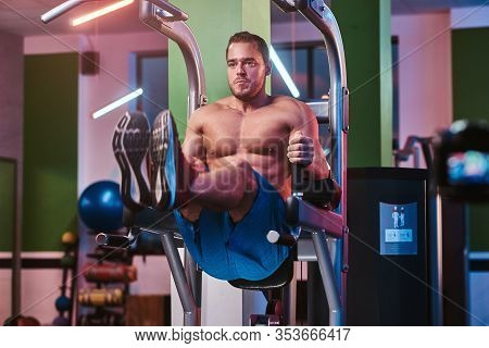 Masculine Bodybuilder Doing Abdominal Excersises On A Parallel Bars, Pumping His Abs In A Modern Fit