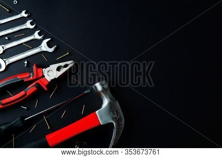 Construction Tools For Home Renovation On Black Background. Red Hammer, Pliers, Screwdriver, Wrenche