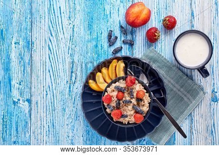 Mug with yogurt and oatmeal porridge with fresh berries and fruit in dark blue bowl on blue wooden background. Top view with copy space. Concept of healthy lifestyle, healthy food, dieting