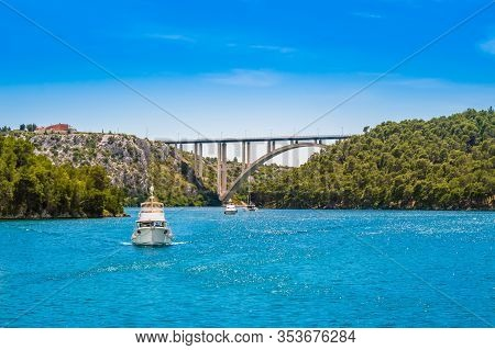 Tourist Boats In Krka National Park, Croatia. Sibenik Bridge Over Krka River With Clear Water And Bl
