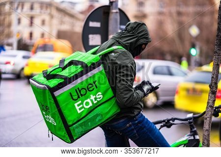 Young Man On A Bike With Uber Eats Logo Delivering Food During A Rainy Day In Bucharest, Romania, 20