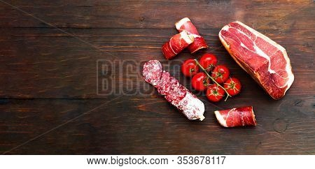 Authentic Italian Prosciutto Dry-cured On Wooden Background. Air-dried Ham And Organic Tomatoes.