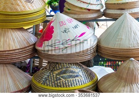 Handmade traditional Vietnamese leaf hats for sale in a market Hoi An, Vietnam, Asia, decorated with the wording Viet Nam in English and Vietnamese.