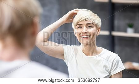 Short Hair Care. Middle-aged Woman Touching Hair Smiling Looking In Mirror Standing In Bathroom Indo