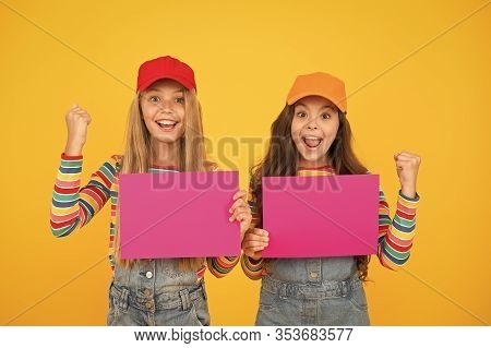 Your Advertising Wins. Happy Small Children Showing Pink Paper Sheets For Advertising On Yellow Back