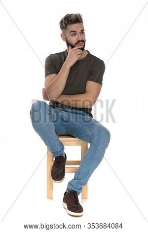 Pensive casual man looking away bothered with his hand on his chin while sitting on a chair on white studio background