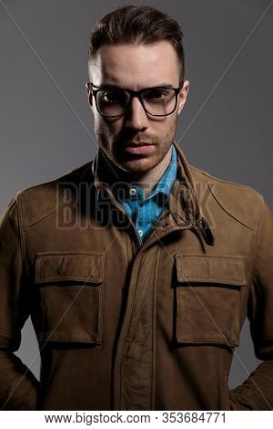 Tough fashion model holding both hands in his pockets while wearing glasses and leather jacket, standing on gray wallpaper background