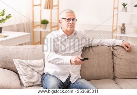 Disappointed By Bad News. Sad Mature Man Watching Tv, Sitting On The Sofa With Remote Controller, Fr