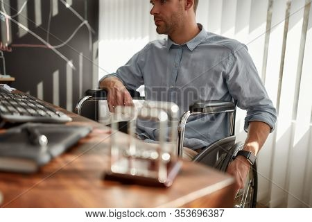 Cropped Photo Of Busy Businessman In A Wheelchair Working At His Workplace In The Modern Office. Dis