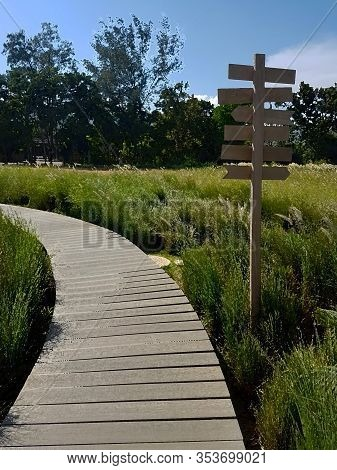 The Vertical Scenery Of The Curved Wooden Bridge Along Into A Green Grass Field And Wooden Guidepost