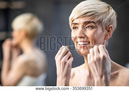 Toothcare Concept. Mature Lady Flossing White Teeth Standing Wrapped In Towel In Bathroom Indoor. Se