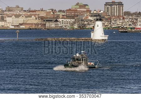 New Bedford, Massachusetts, USA  - March 2, 2020:  Environmental Police patrol boat porpoising over chop from current and stiff southeast breeze inside harbor