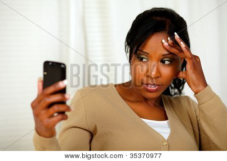 Young Woman With Headache Reading A Message