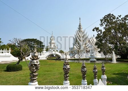 Chiang Rai, Thailand - February.10.2020: White Temple Rong Khun Temple With Skull Fence In Foregroun