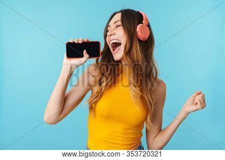 Portrait of beautiful joyous woman wearing headphones listening to music and singing isolated over blue background in studio