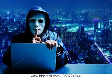 Anonymous Computer Hacker In White Mask And Hoodie. Obscured Dark Face Making Silence Gesture On Mod