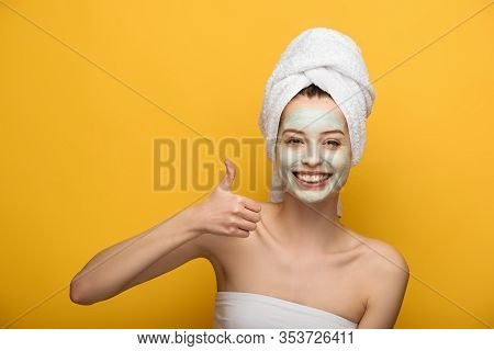 Happy Girl With Nourishing Facial Mask Showing Thumb Up And Smiling At Camera On Yellow Background