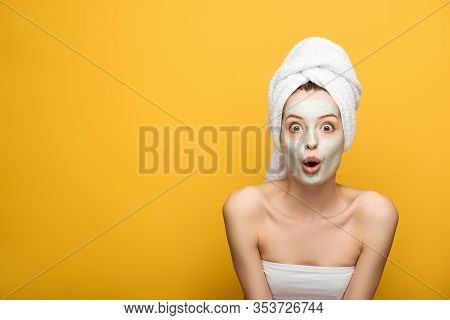 Shocked Girl With Nourishing Facial Mask And Towel On Head Looking At Camera On Yellow Background