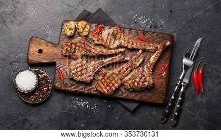 Grilled lamb ribs on cutting board. Hot rack of lamb with spices and condiments. Top view