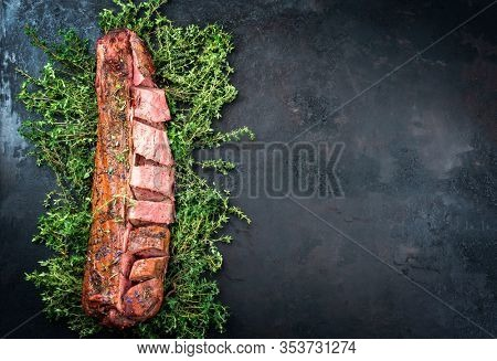 Barbecued dry aged venison tenderloin fillet steak and saddle natural with herbs offered as top view on a rustic board with copy space right