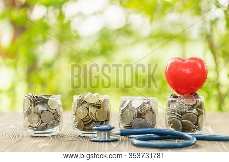 Blue Stethoscope And Jar Of Coin On Wooden Table. Money And Financial Checking Concept