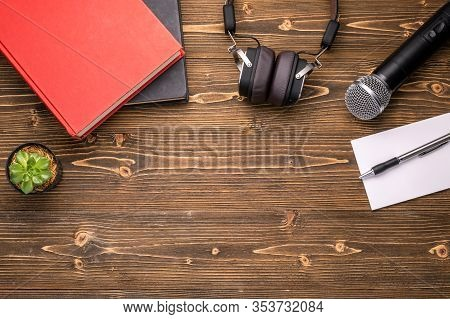 Microphone, Headphone, Book And Paper Note On Brown Wooden Board. Learning About Speaking Concept