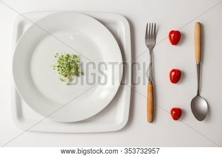 A Small Bunch Of Green Watercress On A Round White Plate And Three Red Cherry Tomatoes Between A For