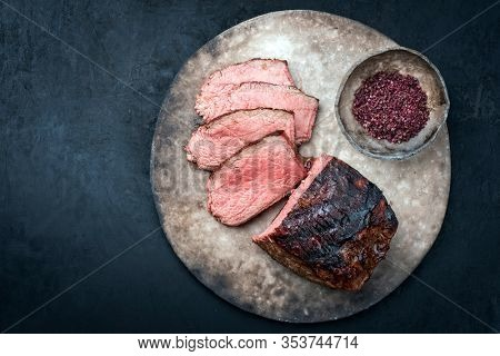 Traditional Commonwealth Sunday roast with sliced cold cuts roast beef with red salt as top view on a modern design plate with copy space
