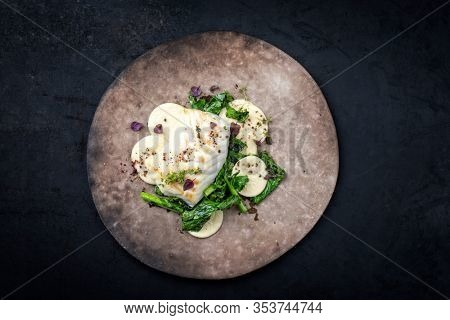 Gourmet fried European skrei cod fish filet with rapini broccoli rabe and creoxetti pasta as top view on a modern design plate with copy space