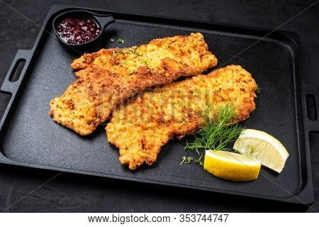 Traditional deep fried Wiener schnitzel from veal topside with cranberry jam and lemon slices offered as closeup on a black modern design tray