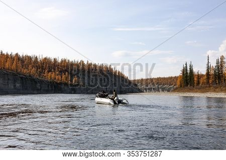 Autumn Rafting On A Boat With Fishing On The Siberian River.  A Fisherman On An Inflatable Boat With