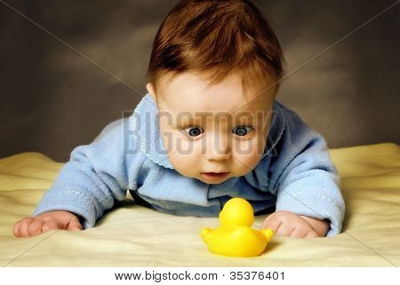 A child with surprise considers a toy duck.