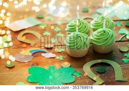 st patricks day, holidays and celebration concept - green cupcakes with candles and other party props on wooden table over festive lights
