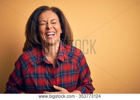 Middle age beautiful woman wearing casual shirt standing over isolated yellow background smiling and laughing hard out loud because funny crazy joke with hands on body.