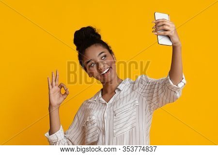 Selfie Fun. Positive Young Afro Woman Taking Self-portrait On Smartphone And Showing Ok Gesture At C
