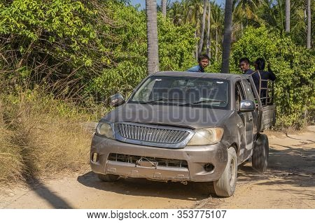 Racha Island, Thailand, January 5, 2020: An Old Wrecked Pickup Truck With Thai Workers In The Back I
