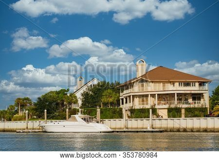 A Nice Three Story Home On A Channel With A Small White Yacht Anchored At Dock