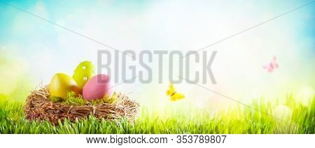 Easter composition with colorful Easter eggs in nest on green grass. Easter concept with copy space.