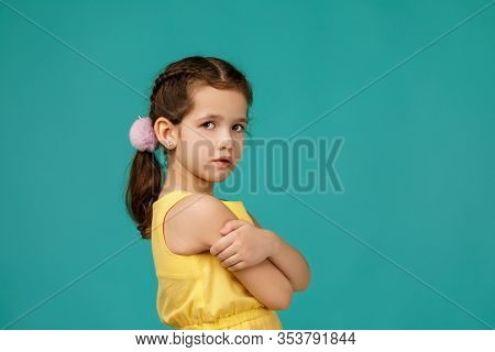 Cute Pensive Liitle Child Girl Stares Intently At The Camera On Blue Studio Background