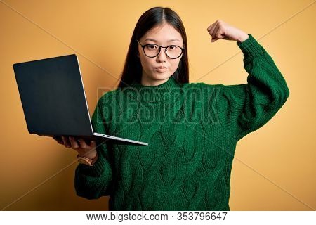 Young asian business woman wearing glasses and working using computer laptop Strong person showing arm muscle, confident and proud of power