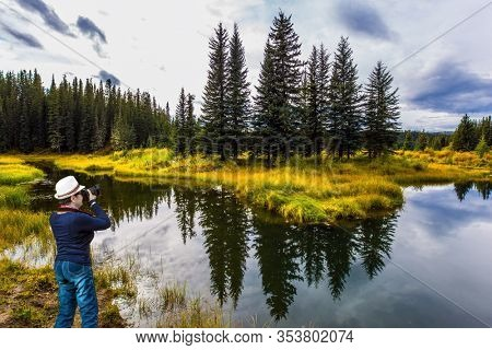 Northern Cordillera. Middle-aged woman in a beautiful hat takes pictures of the lake. Cold cloudy autumn day. The Northern Rocky Mountains. The concept of ecological, active and photo tourism