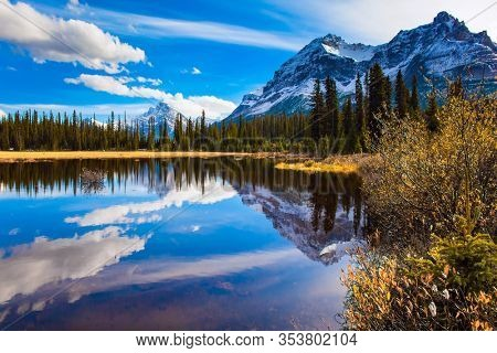 The mountains, forests and lake in the Rockies of Canada. Clouds reflected in the smooth water of the lake. Autumn trip to the Rockies of Canada. The concept of active, eco and photo tourism