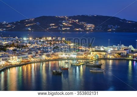 View of Mykonos town Greek tourist holiday vacation destination with famous windmills, and port with boats and yachts illuminated in the evening blue hour . Mykonos, Cyclades islands, Greece