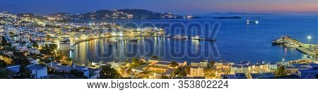 Panorama of Mykonos town Greek tourist holiday vacation destination with famous windmills, and port with boats and yachts illuminated in the evening blue hour . Mykonos, Cyclades islands, Greece