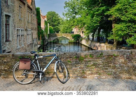Typical Belgian scenic cityscape Europe tourism and bicycle transport concept - bicycle on a bridge near canal and old house. Bruges (Brugge), Belgium