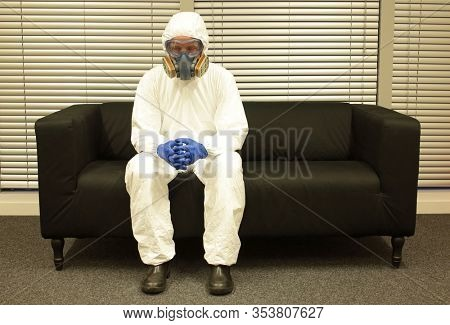 Quarantine. Professional in protective clothing, mask and gloves, sitting on the sofa  and waiting for the end