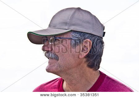 Closeup Of Head & Shoulders Of Grey-Haired Middle Aged Man In Baseball Cap On White Background.