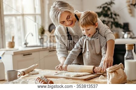 Happy Family Grandmother And Grandson Child  Cook In The Kitchen, Knead Dough And Bake Cookies